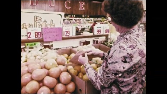 1970s: Woman pushes cart through produce section of grocery store. Woman opens brown paper bag and places oranges in it. Truck pulls trailer with two men on it into orchard.