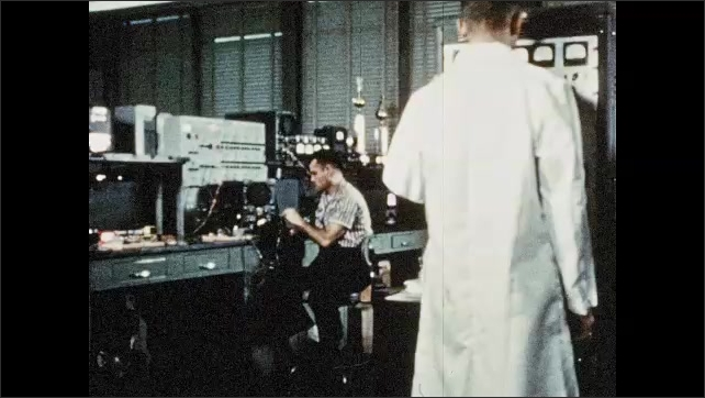 1960s: Man installing machinery. Men working in hangar. Men working on cable. Men in lab, pan to machine moving. Machine moving. Man raises machine.