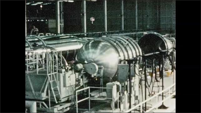 1960s: Rocket engine blasting. Close up of engine. Fuel tanks in hangar. Man puts piece of equipment on tank.