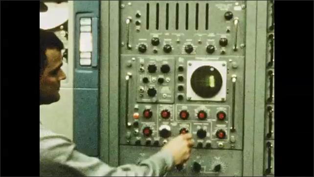 1960s: Men inside launch facility. Men walks past equipment, men working. Man adjusts dial. Waves on screen. Man kneels by equipment.