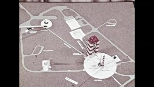 1960s: Pointer indicates different parts of the rocket launching complex. Man points at control center on map.
