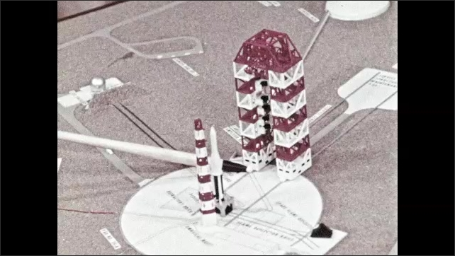 1960s: Close up of model and map of rocket service tower and launchpad.