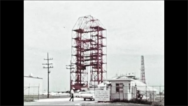 1960s: Car entering secure gate of facility. Rocket platform and launch control center.