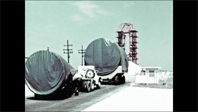 1960s: Caravan of rocket parts on trailers travels down road and through gate of complex.