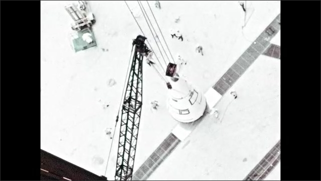 1960s: Nose cone is hoisted by crane. Two men in hard hats and NASA lab coats look up and discuss nose cone.