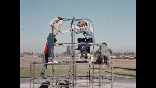 1960s: boys and girls play on playground equipment at park. boys spin around on metal merry-go-round. kids climb dome. students slip down tall slide in sand. kids grab monkey bars.