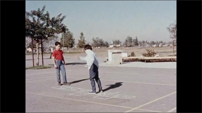 1960s: boy pushes as girl swings in seat and jumps off into sand at swing set. kids throw a rock on pavement and hop on chalk outline of hopscotch game at playground in park.
