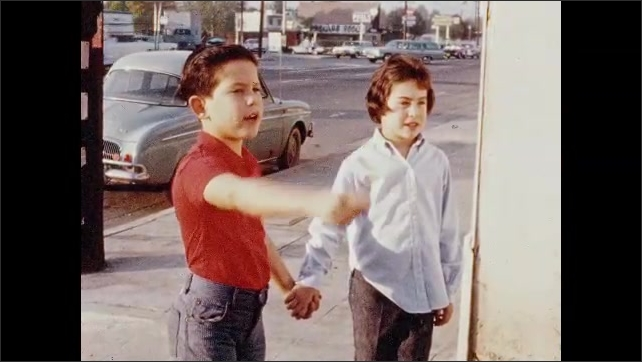 1960s: boy and girl hold hands and walk on sidewalk near trees in suburban neighborhood. brother and sister stroll past businesses, stop and point. trash can sits in alley. kids back up and walk away.