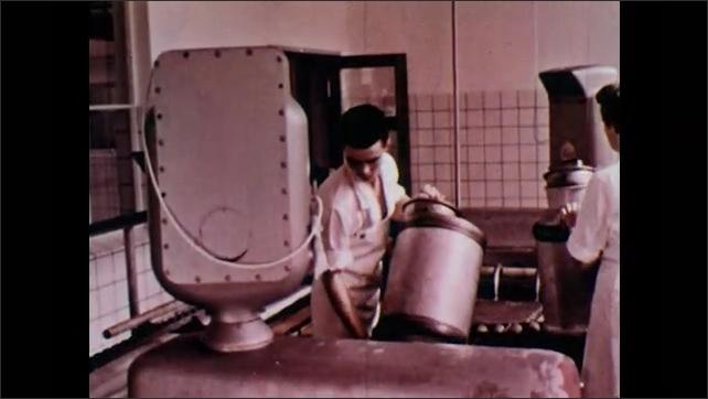 1960s: Men unload milk cartons from cart onto loading dock. Cartons go down conveyor belt. Man and woman assist on conveyor belt. Milk is poured into machine.