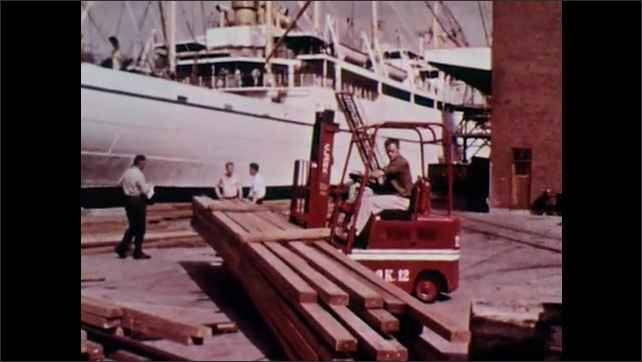 1960s: crane scooping rocks to dump in container, forklift and crane moving wooden planks, carpenter working on chair, man inspecting chair