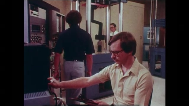 1980s: Split screen of metal piece and thermal image. Men working in lab. Man sculpting with clay. Hands sculpt steering wheel. Low angle view of man sculpting.