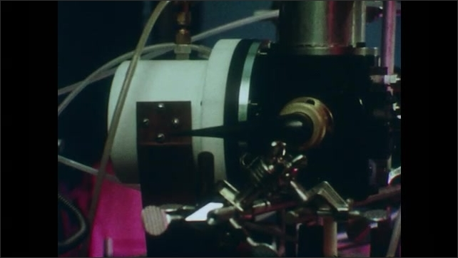 1980s: View of flame through screen. Man on computer in lab. Close up of equipment, pan to man in lab. Low angle view of windmills turning.