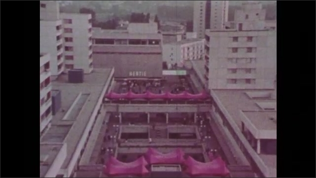 1980s: Girl rides bike through park. People walk through city. People walk on overpass. City skyline. People argue on TV. Hands solder circuitboard. Hands place basket in acid. Car rolls from ramp.