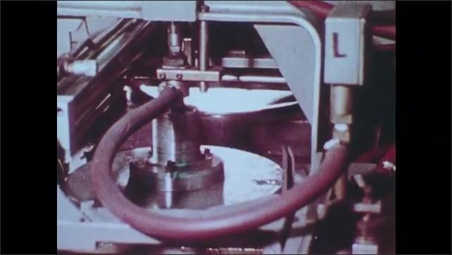 1980s: Gears spin. Crackers move along conveyor belt, Water fall. Hands work in medicine lab. People walk among buildings. People ride escalator. Water swirls in treatment plant tank.