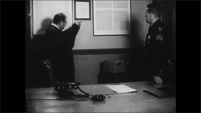 1960s: Office.  Judge speaks to police officer.  Man points to poster.