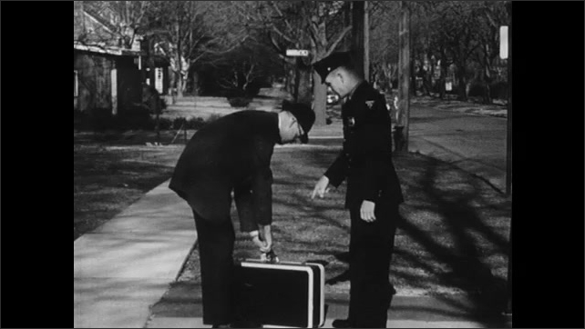 1960s: Neighborhood.  Police officer speaks to man.  Officer points to briefcase.  Man opens briefcase.