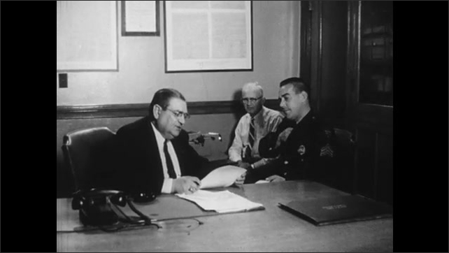 1960s: Office, man types search warrant on typewriter. Man, police officer sit, take warrant, talk, place it on table, sign it.