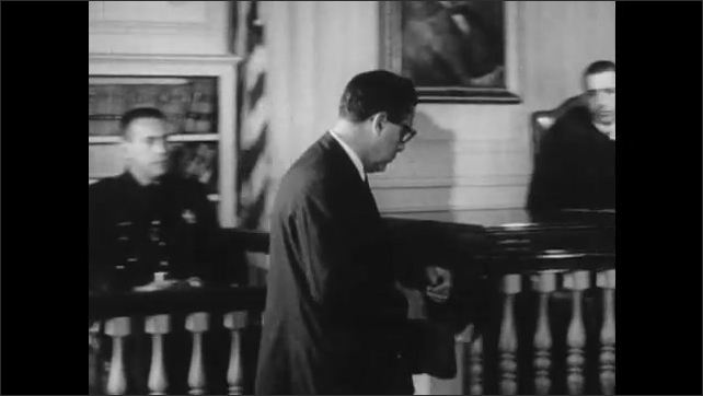 1960s: Courtroom, lawyer puts on glasses, points, talks, police officer sits in witness stand, nods. Judge looks at suspect, suspect shrugs, bites fingernails. Lawyer presents fur coat to judge.