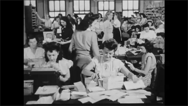 1950s: UNITED STATES: mail order advert for muscle building products. Ladies sort through mail.
