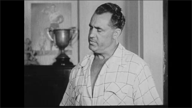 1950s: UNITED STATES: Mr. Atlas sign on door. Man speaks to family.