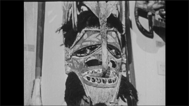 1950s: UNITED STATES: man gives tour to visitors at museum. Man speaks to people at museum. Tribal masks at museum. Campaign of Good Humor pamphlets.