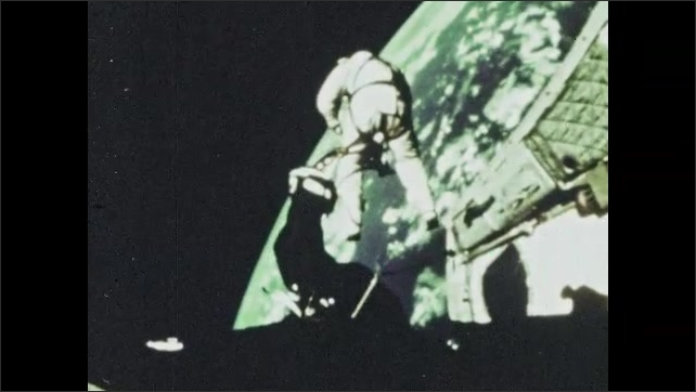1960s: NASA astronaut Edward White floats away from open compartment door in Gemini 4 capsule to space walk during orbit of Earth as cords connect spacesuit to spaceship during mission.