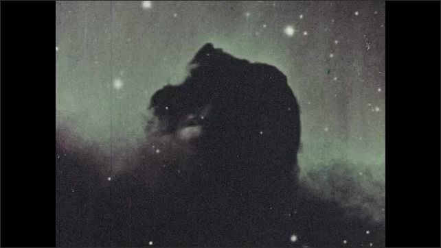 1960s: Horsehead Nebula rises from clouds near stars in space. men in eyeglasses and suits look at paper and check inside metal space telescope with lens in laboratory workshop.