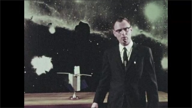 1960s:  man in suit and eyeglasses talks, stands in front of poster of Horsehead Nebula and adjusts model of orbiting astronomical observatory with solar panels. men in safe suits work on satellite.