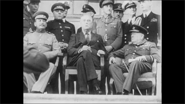1940s: A US military Jeep drives up a driveway. Joseph Stalin, Winston Churchill, and Franklin Roosevelt sit on the porch of a building with men behind them. Close up on Stalin, smiling calmly.