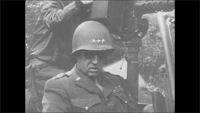 1940s: General George Patton walks past a dog and gets into a Jeep with a shotgun post. Trucks drive by a line of tanks.