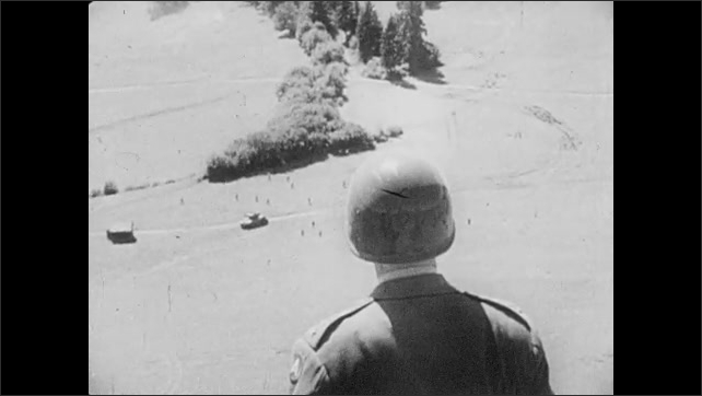 1940s: General George Patton looks through binoculars. Soldiers run across field with guns. Patton on a hilltop looking down at soldiers. Adolf Hitler and officers unfold a map, look at it.