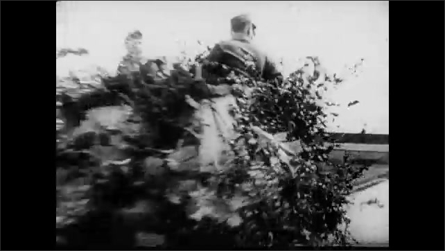 1940s: Hitler and his generals have a good laugh. German tanks go through the streets, some covered in foliage-camouflage. Nazi troops march next to a river.