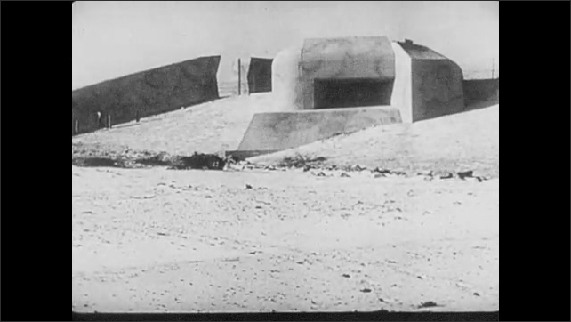 1940s: Variety of defensive structures on the beach. A look-out tower. The barrel of a cannon. A Nazi tank.