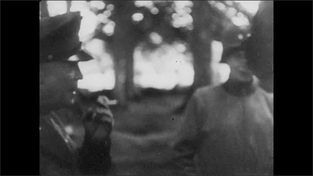 1940s: Dwight D. Eisenhower stands, talks with soldiers, holds a cigarette. Over the shoulder of an officer looking at a map.