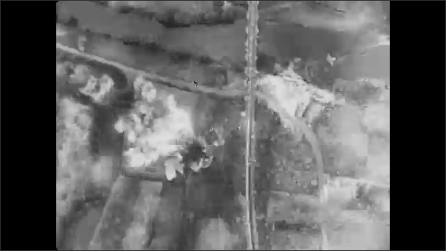 1940s: Airplanes fly overhead. Bombs drop from airplanes. Overhead of bombs dropping, explosions below. Explosions in the sky, overlooking the countryside.