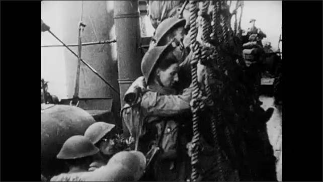 1940s: Allied soldiers by the dozens climb aboard a battleship by bridge and by climbing a rope ladder. Waves crashing.