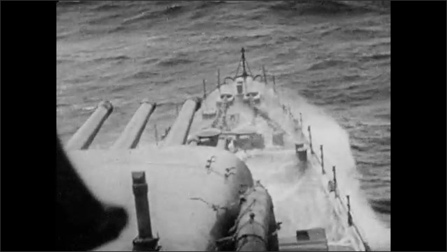 1940s: Bow of a battleship crashing through waves. Ocean spray. Waves crash over boat. Water sprays over dozens of soldiers on board.
