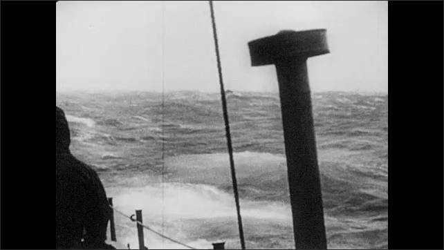1940s: Ships on the ocean. A soldier flashes a spotlight. Man spins nautical mechanism. Boat wake. Nazi meteorologists watch a weather balloon. Weather blimp in sky.