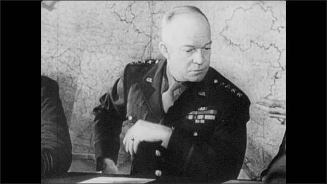 1940s: Dwight D. Eisenhower, Trafford Leigh-Mallory, Bertram Ramsay, Bernard Montgomery and allied generals sit around a conference table. Eisenhower looks at a note and tucks it in his pocket.