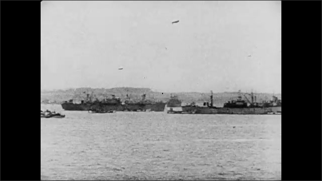 1940s: Panning across dozens of battleships, tugboats, minesweepers and other vessels on the ocean, a blimp flies overhead.