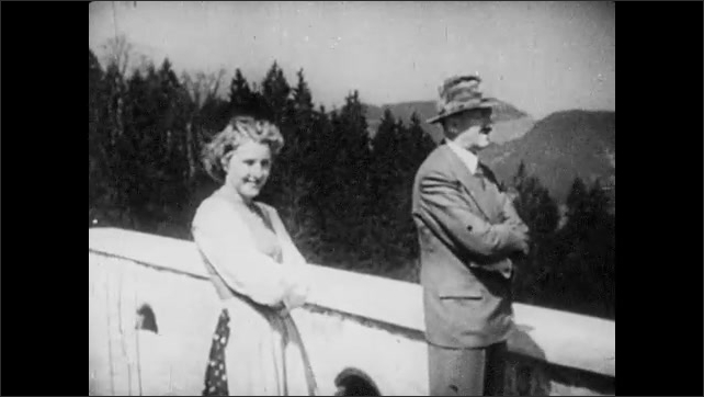 1940s: Adolf Hitler with crossed arms and fedora on veranda. Eva Braun smiles and laughs. They stand with arms crossed. Waves crash along beach. Soldier looks out at ocean. Soldier walks with rifle.