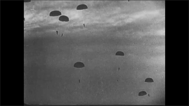 1940s: Airplanes overhead with paratroopers and parachutes below. Paratroopers float through the air. They land on the ground. Soldiers run over hills. Lights flash.