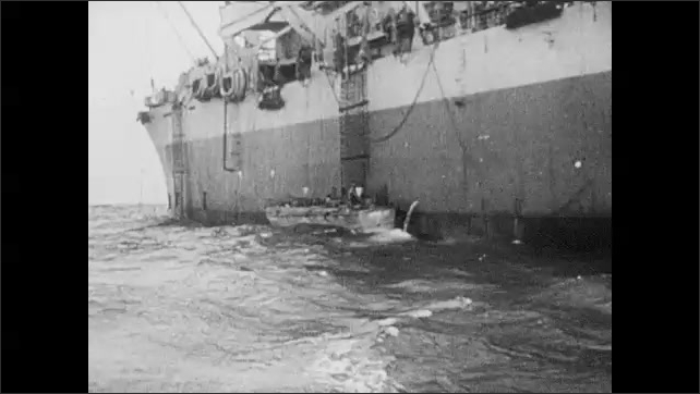 1940s: Beachside cave with cannon and Nazi soldiers. Two soldiers in coastal outpost. Two soldiers walk on beach. Warships at sea. Allied troops climb rope ladders into landing boats. Boats take off.