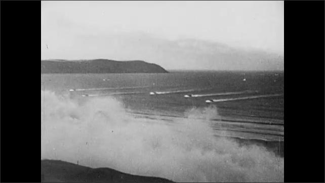 1940s: Allied landing vessels on choppy seas. Several boats approach the smoking Normandy shoreline. Nazi sniper looks through binoculars, readies machine guns.