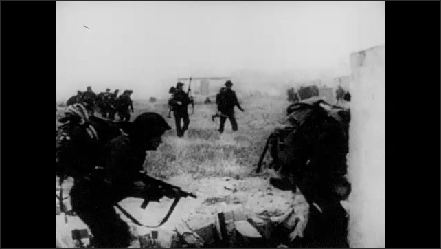 1940s: Allied soldiers run on beach. Troops march by the dozens. Snipers with berets wait in fox hole. Soldiers run past building, through woods. Nazi snipers shoot machine guns.