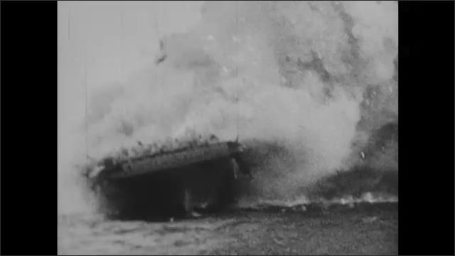 1940s: Plane bursts into flames and crashes near ship. Bomb explodes on deck of ship. Smoke pours from damaged aircraft carrier.