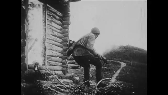 1940s: Soldiers fire artillery. Smoke rises from destroyed town. Men rush into burning town. Soldier throws grenade. Soldiers run near burning town.