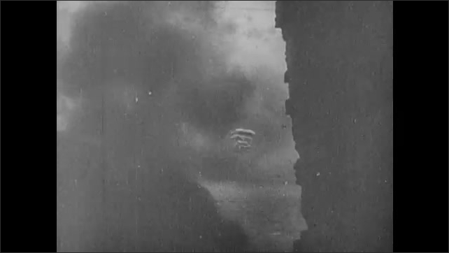 1940s: Soldiers run past barbed wire and into ruined village. Soldiers throw grenades from trench. German soldiers run through burning village. Sniper fires rifle. Soldier falls in street.