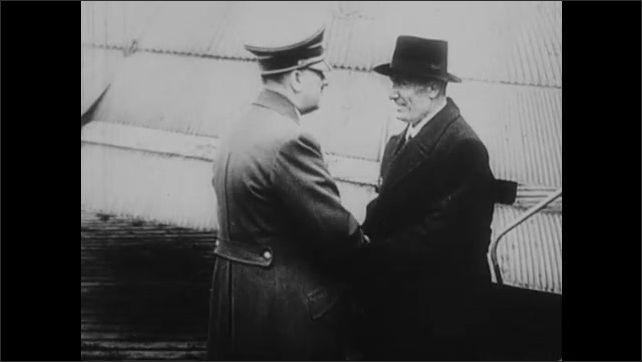 1940s: Nazi plane lands. Mussolini greets Hitler on airstrip. Mussolini and Hitler walk through German military base and talk.