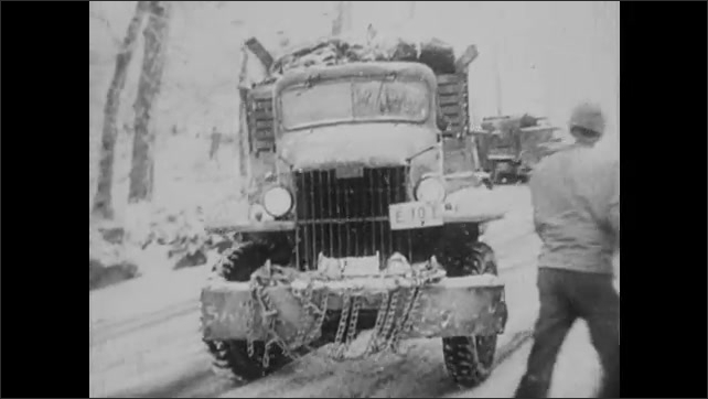 1940s: Trucks drive through flooded and muddy streets. Truck slides down icy road in snow. Nazis stand on snow covered mountain. Nazi soldiers fire guns and mortars from mountainside.
